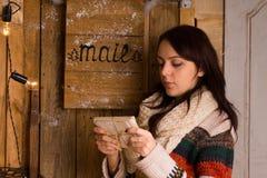 Vrouw die brieven van de brievenbus onderzoeken Stock Foto