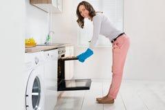 Vrouw die Brood in Oven zetten stock afbeeldingen