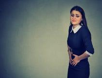 Vrouw die buikpijnmaagpijn of menstruele klemmen hebben stock foto's