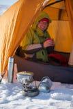 Vrouw die buitentent in wintertijd koken Stock Foto's