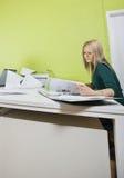 Vrouw die in bureau tegen groene muur werken Stock Afbeeldingen