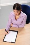 Vrouw die in bureau werkt dat bij haar bureau schrijft Stock Foto's