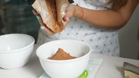 Vrouw die cacao toevoegen aan kom voor het koken van naar huis gemaakte chocolade stock footage