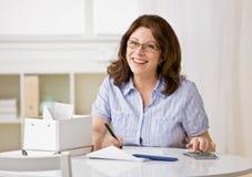 Vrouw die calculator gebruikt om maandelijkse rekeningen te betalen Royalty-vrije Stock Foto's