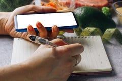 Vrouw die calorie tegentoepassing op haar smartphone gebruiken stock afbeelding