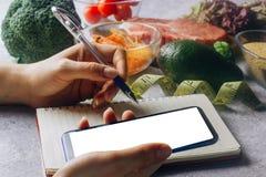 Vrouw die calorie tegentoepassing op haar smartphone gebruiken royalty-vrije stock foto's