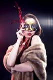 Vrouw die Carnaval Venetiaans masker op onduidelijk beeldachtergrond dragen Stock Foto