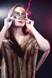 Vrouw die Carnaval Venetiaans masker op onduidelijk beeldachtergrond dragen.   Stock Foto's