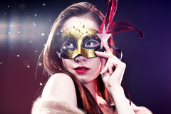 Vrouw die Carnaval Venetiaans masker op onduidelijk beeldachtergrond dragen.   Royalty-vrije Stock Foto