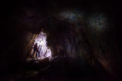 Vrouw die caver spelunker het hol onderzoeken stock fotografie