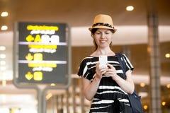 Vrouw die celtelefoon in luchthaven met behulp van Royalty-vrije Stock Foto's