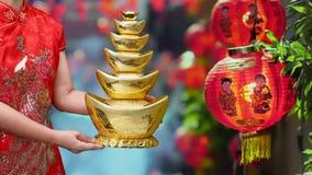 Vrouw die Chinese nieuwe jaar gouden ingotsin houden chinatown