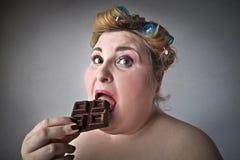 Vrouw die chocolade eet Stock Afbeeldingen