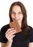 Vrouw die Chocolade en het Glimlachen eet Stock Foto