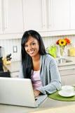Vrouw die computer in keuken met behulp van Stock Foto
