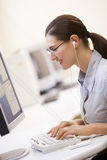 Vrouw die in computerzaal aan MP3 Speler luistert Royalty-vrije Stock Afbeelding