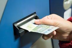 Vrouw die Contant geld opnemen in Machine stock foto's