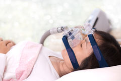 Vrouw die CPAP-masker, de obstructieve therapie van slaapapnea dragen, bokeh achtergrond royalty-vrije stock afbeelding