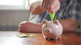 Vrouw die creditcard zet in spaarvarken Het concept besparingsgeld en investering stock footage