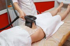 Vrouw die cryolipolysis vette behandeling in professioneel kosmetisch kabinet krijgen stock foto