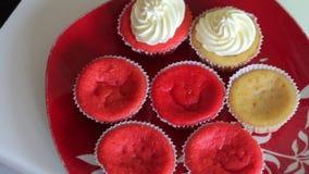 Vrouw die cupcake rood fluweel voorbereiden Pas de room met een gebakjezak toe De gebe?indigde cakes zijn op de plaat Close-up stock videobeelden