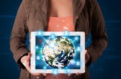 Vrouw die 3d aardebol in moderne tablet voorstellen Stock Afbeeldingen