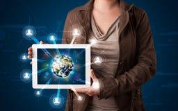 Vrouw die 3d aardebol in moderne tablet voorstellen Stock Foto