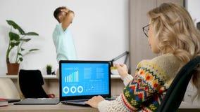 Vrouw die de analyse van bedrijfgegevens van geanimeerde grafiek bestudeert terwijl haar echtgenoot heel wat lawaai op de achterg stock video