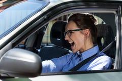 Vrouw die de auto en het gillen tegenhouden Stock Afbeeldingen