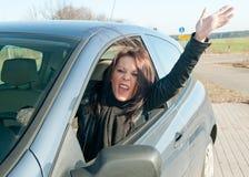 Vrouw die in de auto gilt Stock Afbeeldingen