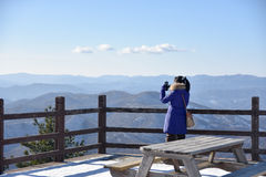 Vrouw die de berg bij de winter van pijler bekijken Gekleed in bl Royalty-vrije Stock Foto's