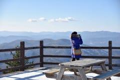 Vrouw die de berg bij de winter van pijler bekijken Gekleed in bl Royalty-vrije Stock Fotografie