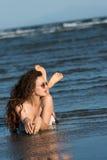 Vrouw die in de bikini van de zeewaterslijtage, zonnebril en wit overhemd liggen stock foto
