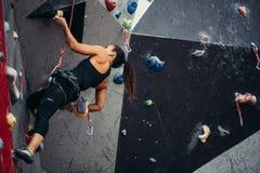 Vrouw die de bovenkant van kunstmatige bouldering muur bereiken terwijl het uitoefenen in gymnastiek stock fotografie