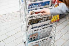 Vrouw die de Duitse krant van Matrijzenzeit met Angela Merkel kopen royalty-vrije stock afbeelding