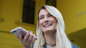 Vrouw die de functie van de smartphonespraakherkenning het online lopen op een stadsstraat, die aan mobiele medewerker gebruiken  stock videobeelden