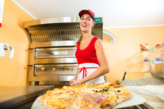 Vrouw die de gebeëindigde pizza van de oven duwen Stock Foto's
