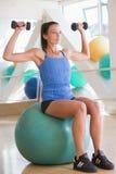 Vrouw die de Gewichten van de Hand op Zwitserse Bal gebruikt bij Gymnastiek Royalty-vrije Stock Foto's