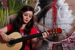 Vrouw die de gitaar speelt Stock Foto's