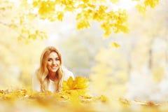 Vrouw die in de herfstpark leggen Stock Afbeeldingen