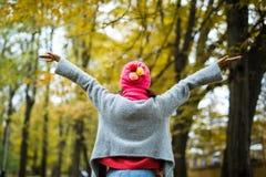 Vrouw die in de herfstpark loopt stijg haar handen royalty-vrije stock afbeelding