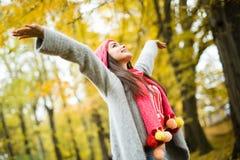 Vrouw die in de herfstpark loopt stijg haar handen stock afbeelding