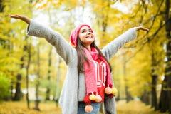 Vrouw die in de herfstpark loopt stijg haar handen royalty-vrije stock foto
