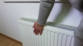 Vrouw die de het verwarmen radiator controleren stock video