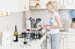 Vrouw die in de keuken werkt Stock Fotografie