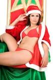 Vrouw die de kleren van de Kerstman in haar leunstoel draagt Royalty-vrije Stock Foto's