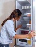 Vrouw die in de koelkast kijken stock foto's