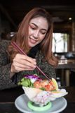 Vrouw die de kruidige salade van de zalmsashimi in restaurant eten stock afbeeldingen