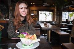 Vrouw die de kruidige salade van de zalmsashimi in restaurant eten stock afbeelding