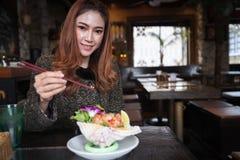 Vrouw die de kruidige salade van de zalmsashimi in restaurant eten stock foto's